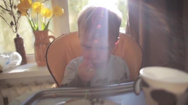 Rozkošný, roztomilý chlapeček vysoké židli, jíst, smát a usmívat se v sluneční paprsky před velké okno