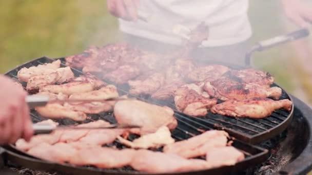 Mans vaření kuřecí na grilu venku v létě. Dým z grilovaného masa