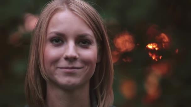 Portrét mladé ženy, která stojí u parku v paprscích zapadajícího slunce, při pohledu na fotoaparát a s úsměvem, detail