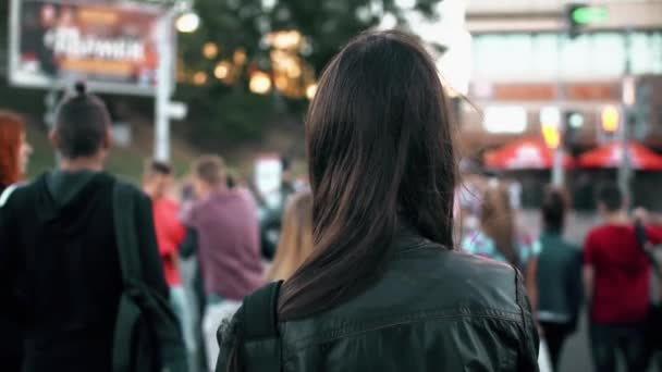 Young woman standing on street, preparing cross road at traffic lights, hair fluttering in the wind. Back view. Slow mo