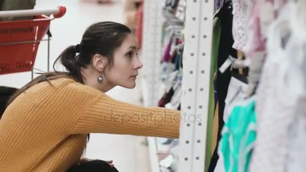 47eb5098e Mujer hermosa joven en cuclillas en el supermercado y elegir la ropa del  bebé en el escaparate. Mujer en la tienda. 4k– metraje de stock
