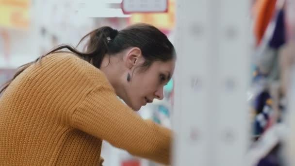 8b72a6fb3 Mujer hermosa joven en el supermercado eligiendo la ropa del bebé en el  escaparate. Mujer en la tienda comprando ropa. 4k– metraje de stock
