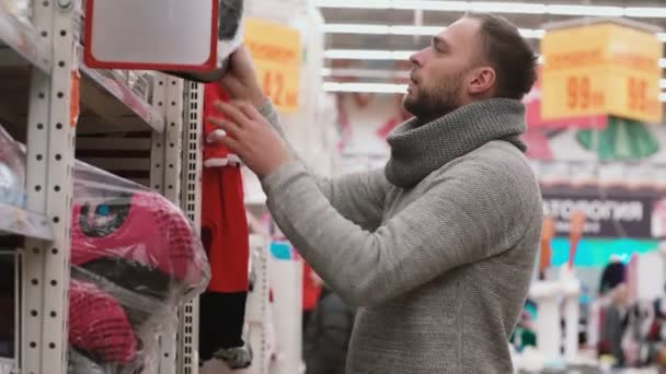 Mladý muž výběru zboží na regálech v supermarketu, chce lehátko vozu Ahoj, kontrola kvality. 4k