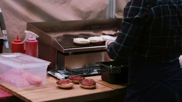 Ein Koch in weißen Handschuhen macht Burger mit frischem Salat und grillt rohes Fleisch für Hamburger auf dem Grill. zurück