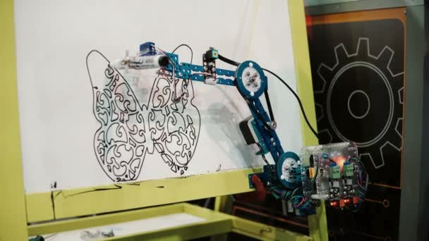 NOVEMBER 5, 2016 RUSSIA, MOSCOW Robotics Expo. Robot draws the stencil, mechanical arm with calligraphy handwriting. 4K