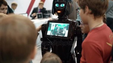 NOVEMBER 5, 2016 RUSSIA, MOSCOW Robotics Expo.Girl robot KIKI in crowd, talking to visitors, show video on screen. 4K