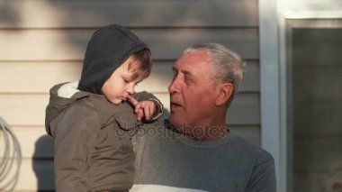 Old man holding on hand little boy. Grandfather and grandson talking, smiling, looking to camera outdoor on sunlight. 4K