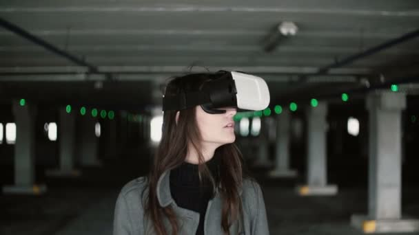 Young woman using a virtual reality glasses on parking place. Girl with waving hair wearing VR headset. 4K