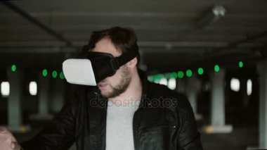 Young man standing in parking place wearing virtual reality glasses. Having fun with VR headset. 4K