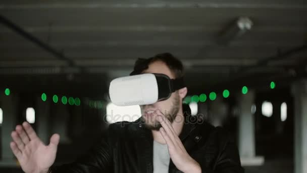 Young man standing in parking place and using virtual reality glasses. Having fun with VR headset. 4K