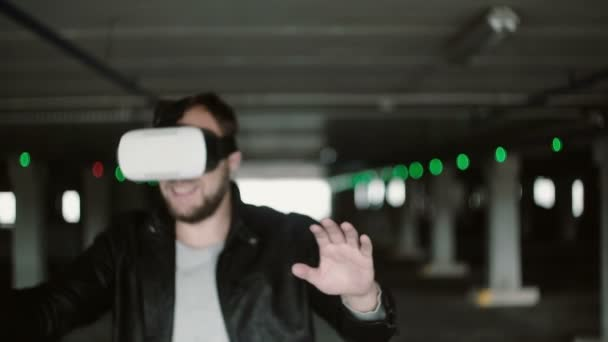 Young man using virtual reality glasses in parking place. Male in VR headset walking through the aisle. 4K
