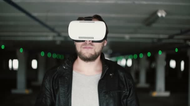 Young man using virtual reality glasses in parking place. Then male take off 3D glasses, looking at camera and smile. 4K