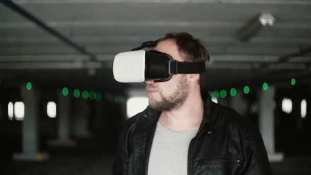 Young man standing in parking place and using virtual reality glasses. Exploring space with VR headset. 4K