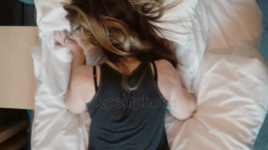 Tip view of angry woman falls face down on the bed in room. Sad girl beating her fist the pillows
