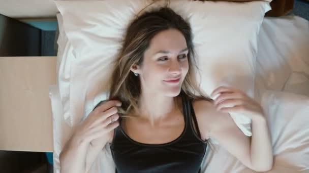Šťastná mladá žena leží na posteli a snít o něčem. Roztomilá krásná dívka hraje s vlasy a myšlení.