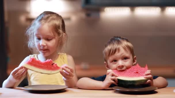 Bratr a sestra sedí u stolu v kuchyni. Chlapec a dívka jíst šťavnatý meloun, při pohledu na fotoaparát