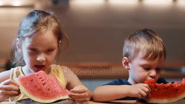 Bratr a sestra sedí u stolu v kuchyni. Chlapec a dívka jíst šťavnatý meloun na desce, kouše kusy