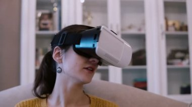 Close-up view of young woman in virtual reality glasses sitting on couch at home. Female looking around in VR-headset.