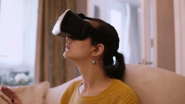 Portrait of young woman in virtual reality glasses sitting on the sofa at home. Female looking around in VR-headset.