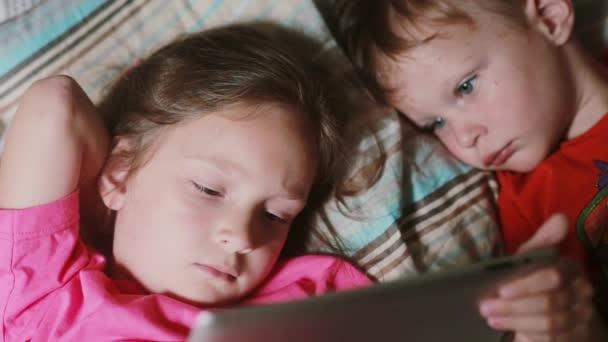 Dívka a chlapec leží na posteli a sleduje kreslené na dotykové obrazovce tabletu. Bratr a sestra spolu s ostatními