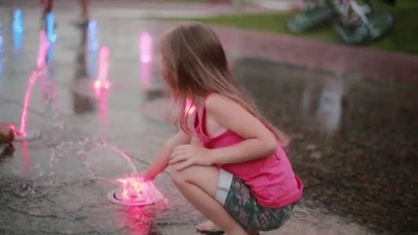 Niedliche kleine Mädchen hocken und spielen mit gefärbtem Wasser-Jets am Brunnen in heißen Sommertag