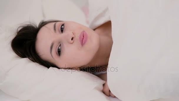 Veselé a svěží brunetka žena v posteli doma. Krásná dívka skryje pod přikrývkou a usmívá se
