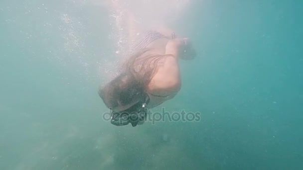 Close-up view young woman swimming underwater with mask. Girl diving in a tropical sea. slow motion.