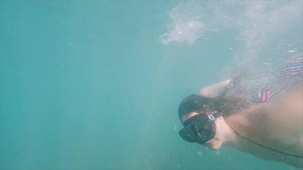 567ed9f22 Jovem mulher com máscara facial mergulha na água. Mergulho no mar tropical