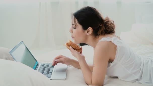 7f261c5f0ff Hermosa chica acostado en la cama en la mañana, con ordenador portátil. Mujer  joven comer croissant, escribir, navegar por Internet– metraje de stock