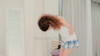 Young happy woman in pajamas dancing. Brunette girl haves fun in front of mirror, looks at the reflection. Slow motion.