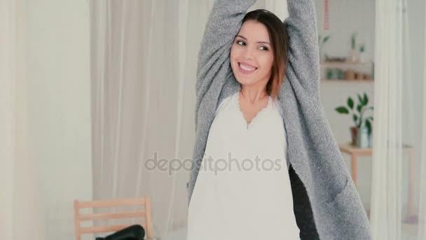 Mladá usměvavá žena nosí pyžamo baví v noci. Brunetka točí a spadne na posteli. Zpomalený pohyb