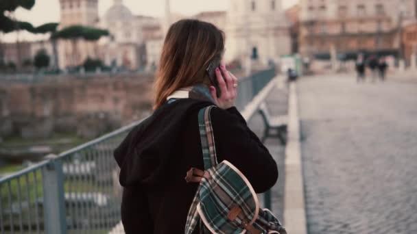 brünette Frau telefoniert während eines Spaziergangs in einem römischen Forum. Mädchen erzählt von der Reise in Rom, Italien.