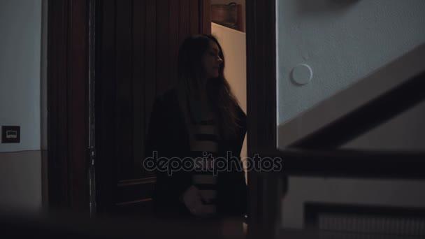 Mladá krásná žena s kufrem opustí byt. Cestovatel dívka přichází dolů na žebříku se zavazadly