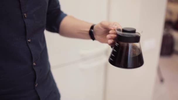 Zár-megjelöl kilátás-ból fiatal barista kávét. Ember rázza fel ital kis szemüveg teáskannát, reggel.