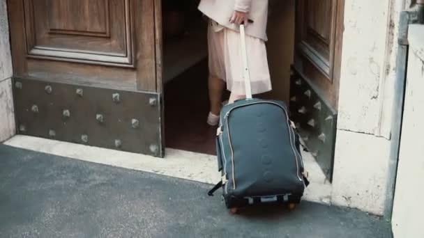 Mladý cestovatel žena chůze s kufrem na ulici. Dívka otevírá dveře a přichází do oblouku