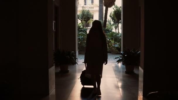 Silueta ženy procházejí temným tunelem. Dívka s kufrem chodí v zahradě, otevírá dveře a zmizí