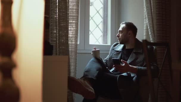 Stylový muž sedí v křesle a při pohledu na okna. Mladý muž používá smartphone v obývacím pokoji a pije kávu
