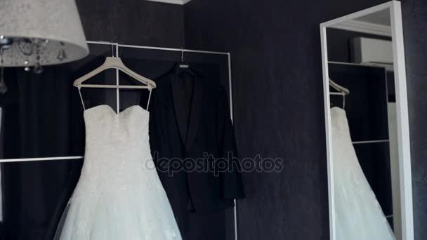 Svatební den. Šaty a obleky, visí v bytě. Příprava k obřadu.