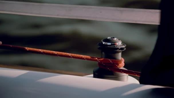Námořník v černém obleku pomocí revolverové hlavy k upevnění lana. Datailní pohled mužských rukou kroucení kabelu