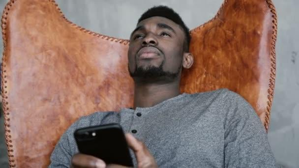 Africký muž sedí v křesle a myšlení, držení Smartphone. Člověk si pamatuje něco dobrého a začne psát zprávy