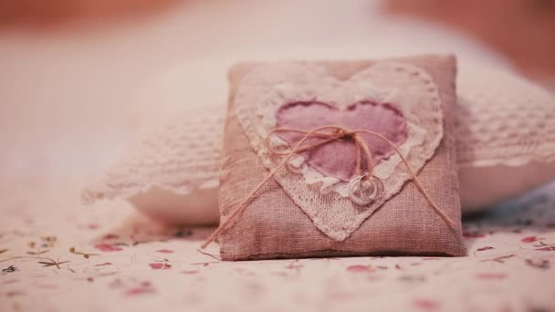 Beautiful wedding rings on a little pillow. Preparation for ceremony, details of wedding in rustic style. Slider right.