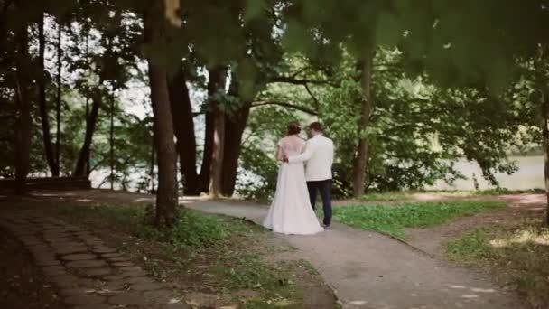 Zadní pohled na šťastný pár v parku na jejich svatební den a polibek na konci. Krásné bílé svatební šaty, šaty