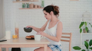 Beautiful young woman in kitchen dancing in the morning. Brunette girl wearing pajamas haves breakfast at home.