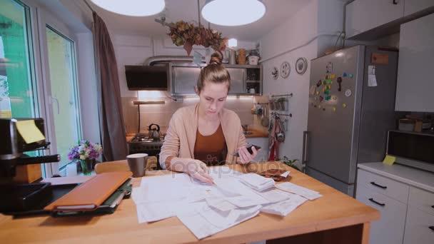 Mladá žena sedí u stolu v kuchyni a výpočet kusovníků. Oddělení domácí účty. Kontrola účtů