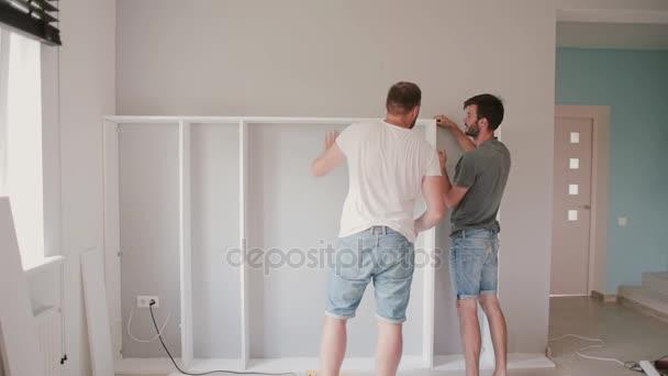 Dva přátelé montáž regálu, opravář. Muž pomáhá svému příteli, stěhování do nového domu