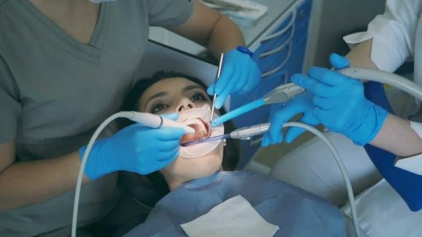 Mladá žena, sedící v zubní křeslo s otevřením široká ústa. Zubař s ošetřovatelkou čištění a leštění zubů