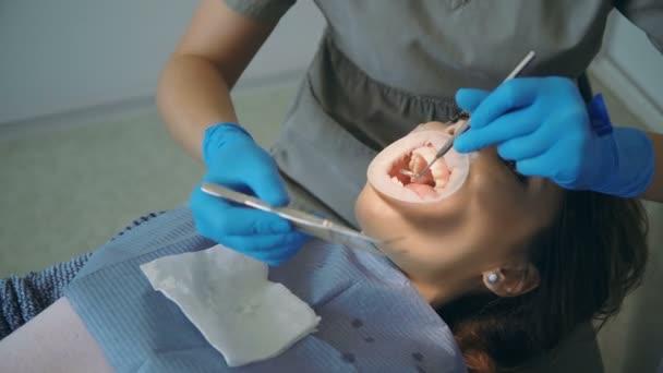 Mladá žena ležící v Zubařské křeslo, zubař úklid a polské zuby. Doktor s sestra si optradam