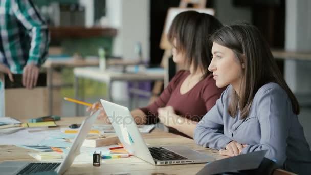 Squadra di piccola impresa creativa lavorando in ufficio di coworking. Due donna parlare, discutere idea e utilizzare il computer portatile