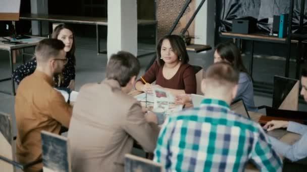 junge multiethnische Gruppe von Menschen, die im Coworking Space arbeiten. Kleines Start-up von Architekten, die Projektideen diskutieren.