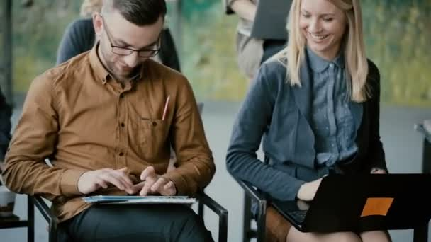 Young happy group of people at business meeting. Man and woman smiling, using gadgets, laptop and digital tablet.